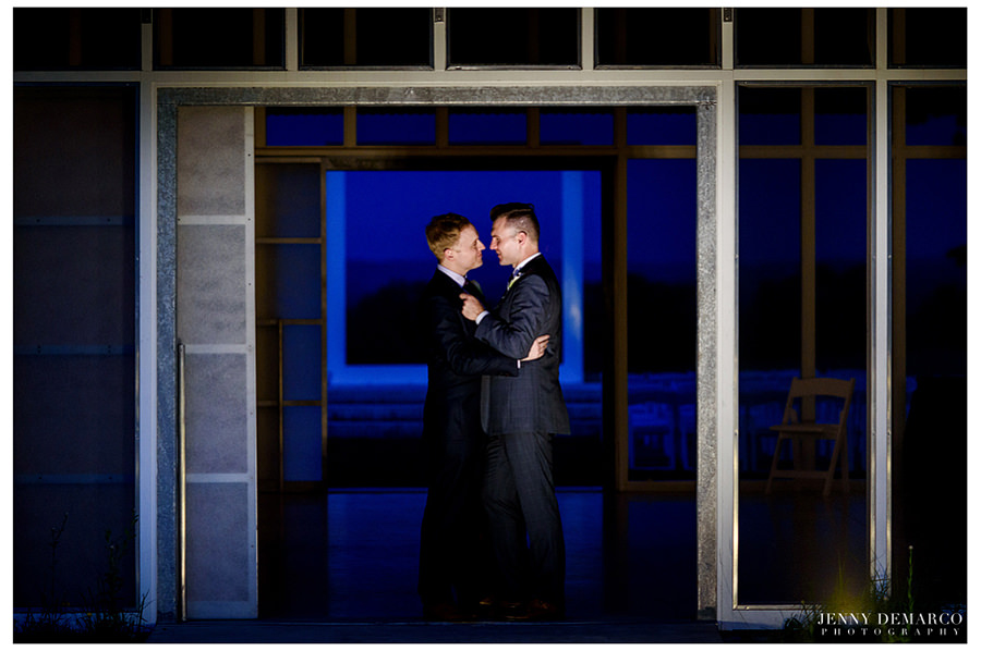 Grooms embrace during night portrait after their wedding reception.