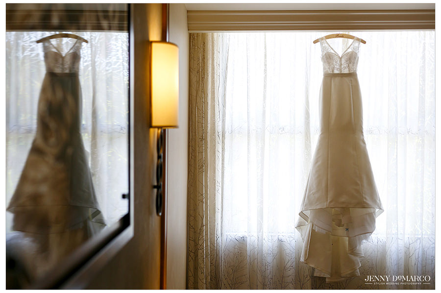 A photo of the wedding dress hung beautifully with the backlight of a window.