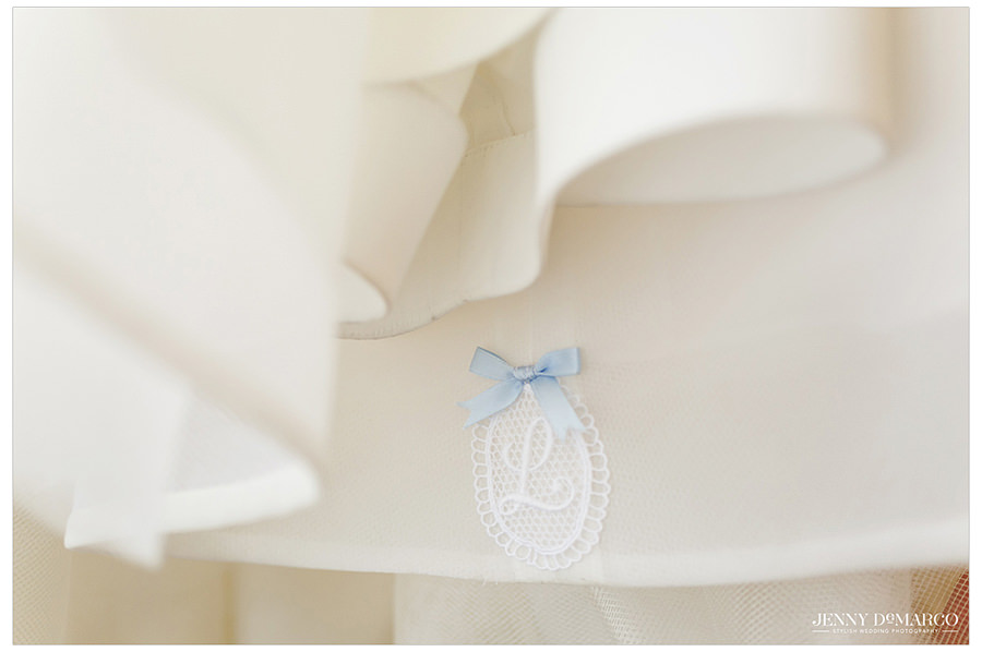 A close up of a blue bow and initial sewn in the bottom of the bride's Carolina Herrera wedding dress.