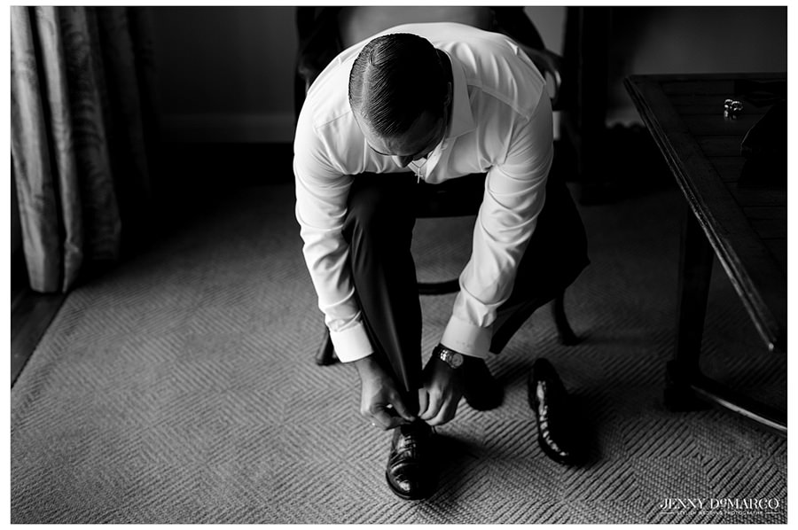 A black and white photo of the groom sitting as he puts his shoes on.