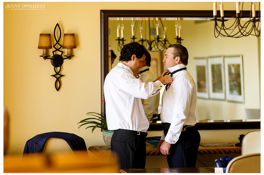 A groomsman helps the groom with his bowtie.
