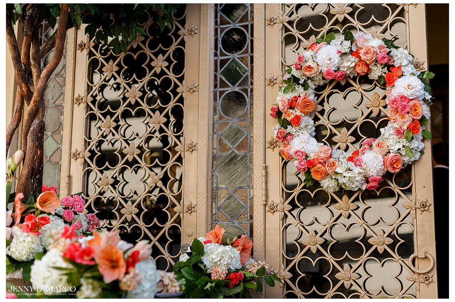 A detail photo of the florals on the outside of the church and the elaborate doors.