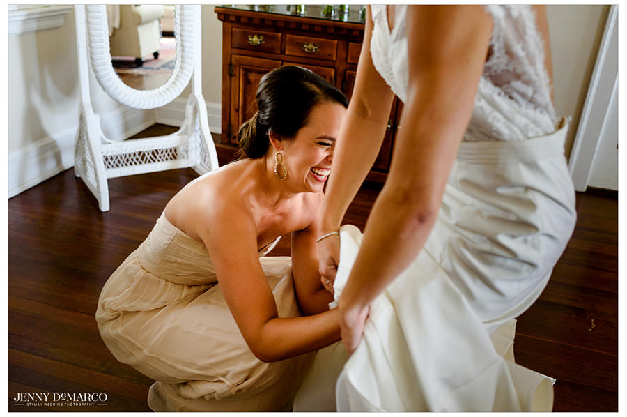 A bridesmaid laughed while helping the bride put her dress on.