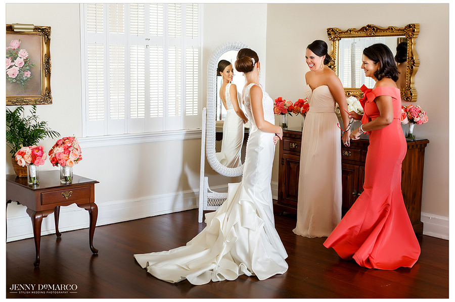 The bride looks at herself in the mirror in her dress with her mother and bridesmaid.