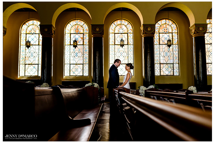 A landscape, detail photo of Central Christian Church with ornate stain glass windows and the couple holding hands as they share a moment before the ceremony.
