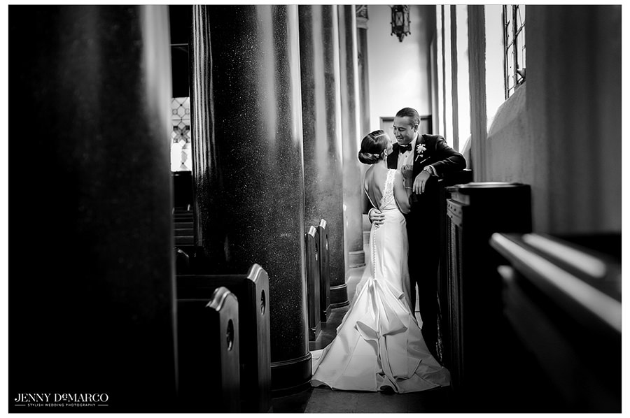 A black and white portrait of the bride and groom looking into each other's eyes.