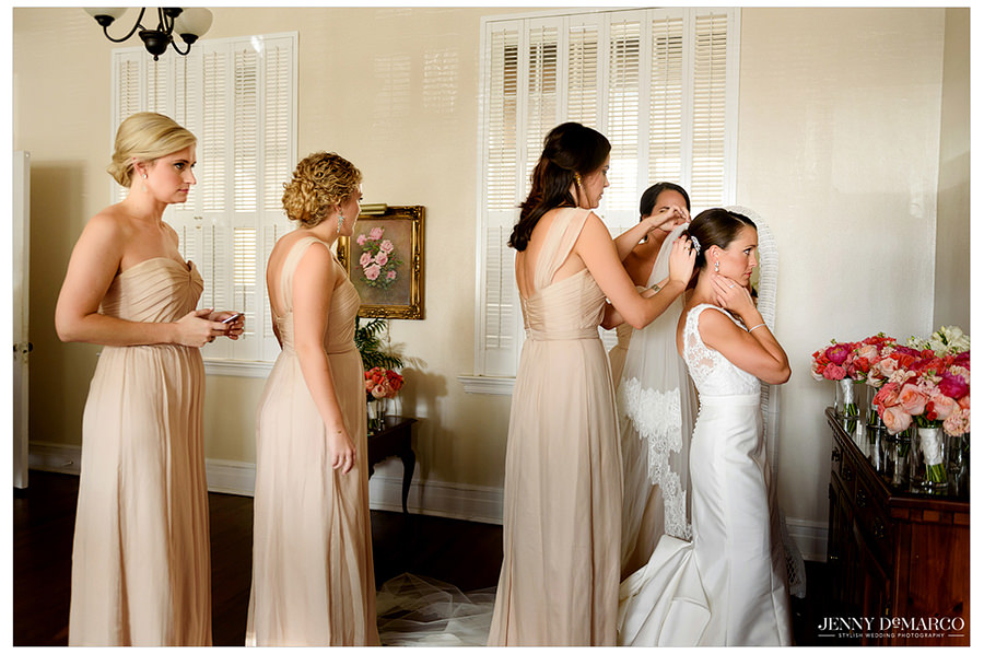 The bride sits as her bridesmaids assist her will placing her veil in her hair.