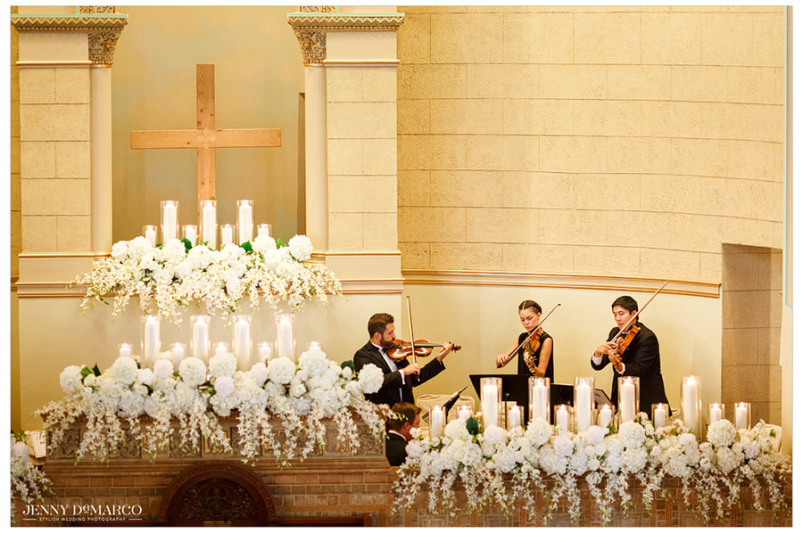 A beautiful picture of the details of the alter of Central Christian Church including a wooden Cross, candles, and white flowers. There are also three violinists playing at the front of the church.