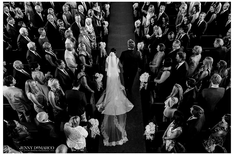 A black and white birds eye view of the church as the guests stand as the bride walked down the aisle with her father.