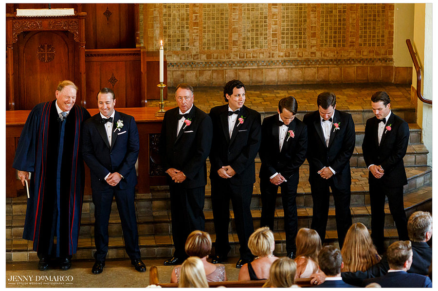 The groom and minister smile together at the alter with all the groomsmen at their side.