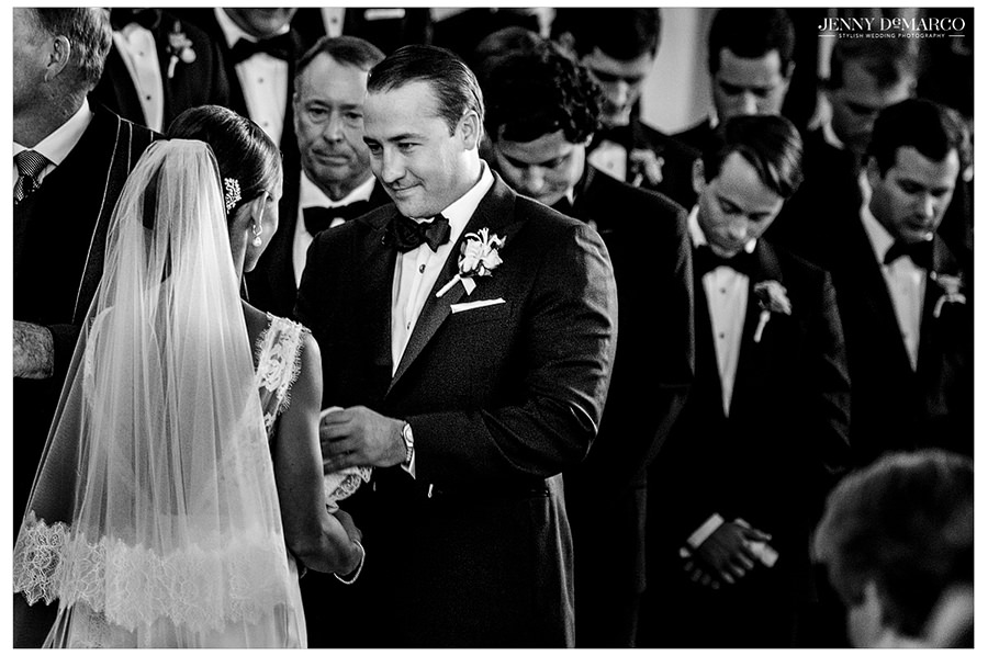 A black and white picture of the groom smiling as he takes the hands of his wife to say a prayer. The rest of the guests bow their heads in prayer.