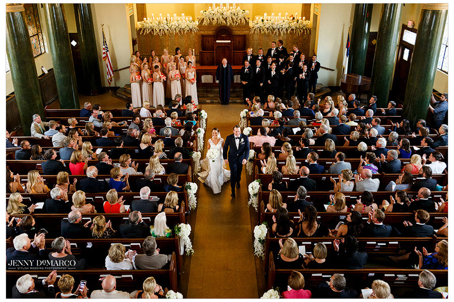 A birds eye view of the guests clapping and smiling up at the couple as they begin their exit down the aisle of Central Christian Church.