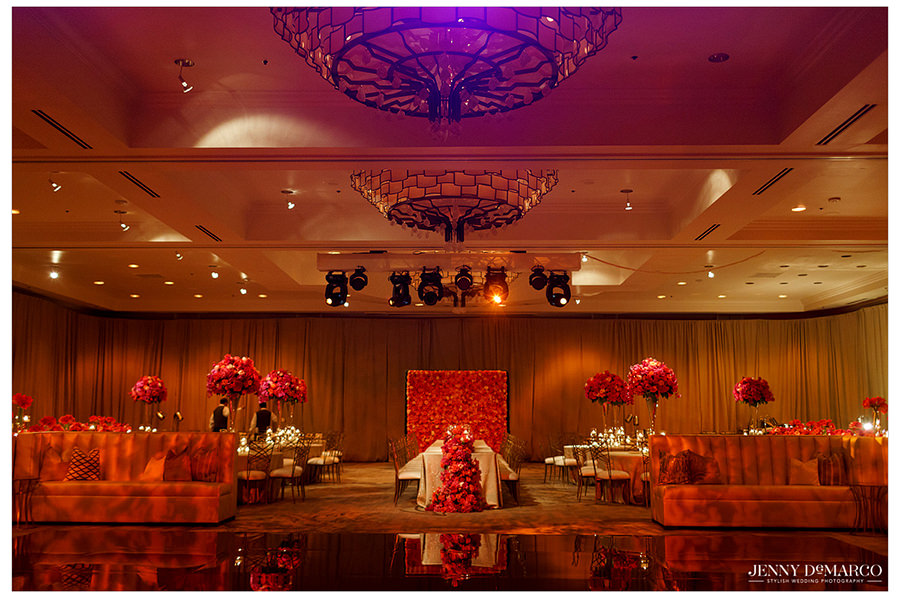 A picture of the whole ballroom at the Four Seasons hotel which is detailed with vibrant red roses and warm colors along the walls and tables. The golden dance floor shimmers and reflects the details of the room.