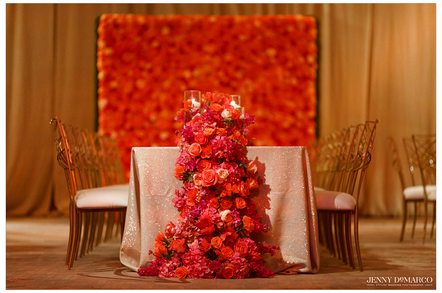 A picture of the head table overflowing with red, pink, and orange roses and candles with a shimmery champagne tablecloth and gold chairs.