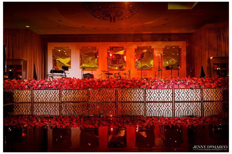 A picture of the stage lined with red roses and rose petals awaiting the band for the reception.