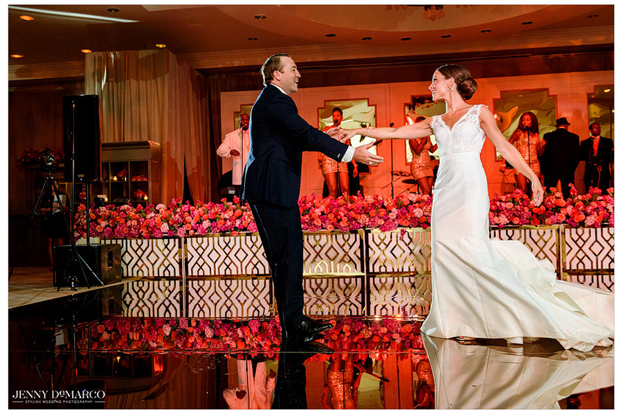 The bride and groom share their first dance as newlyweds on the gold dance floor while the band plays behind them.