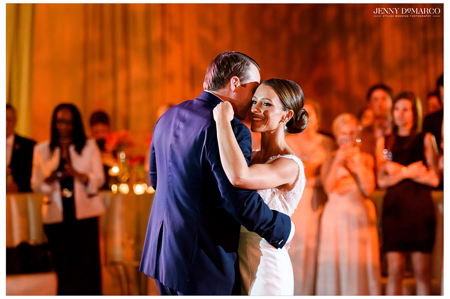 The bride and groom share their first dance as guests watch and smile.