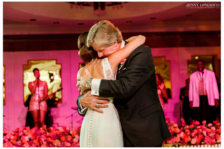 The father of the bride hugs and shares a moment with his daughter after their father daughter dance.