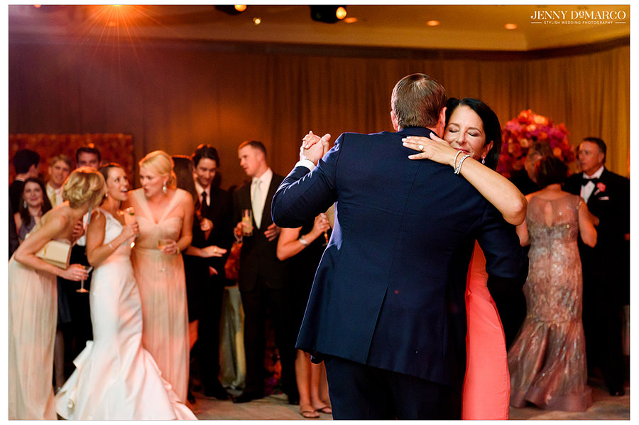 The groom dances with the mother of the bride and the bride watches and smiles with her friends and bridesmaids.