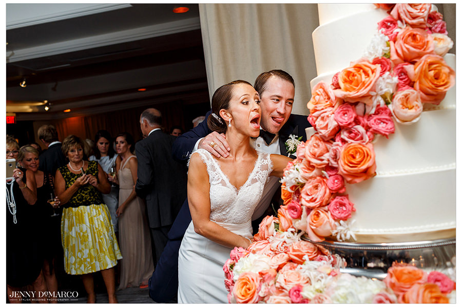 The bride and groom cut the wedding cake together which is details with pink and orange roses to match the other details of the ballroom.
