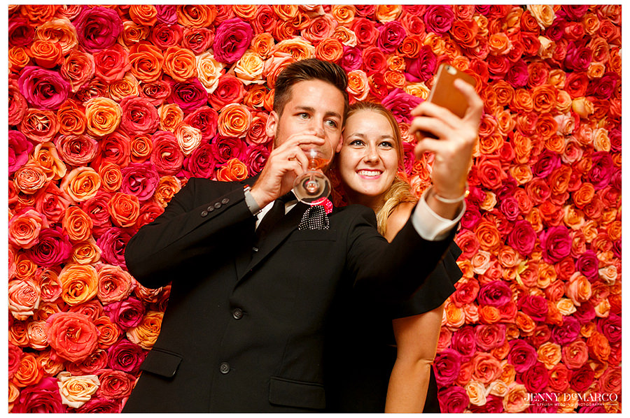 Two guests hold up their drinks and smile to take a selfie in front of the vibrant, red rose wall.