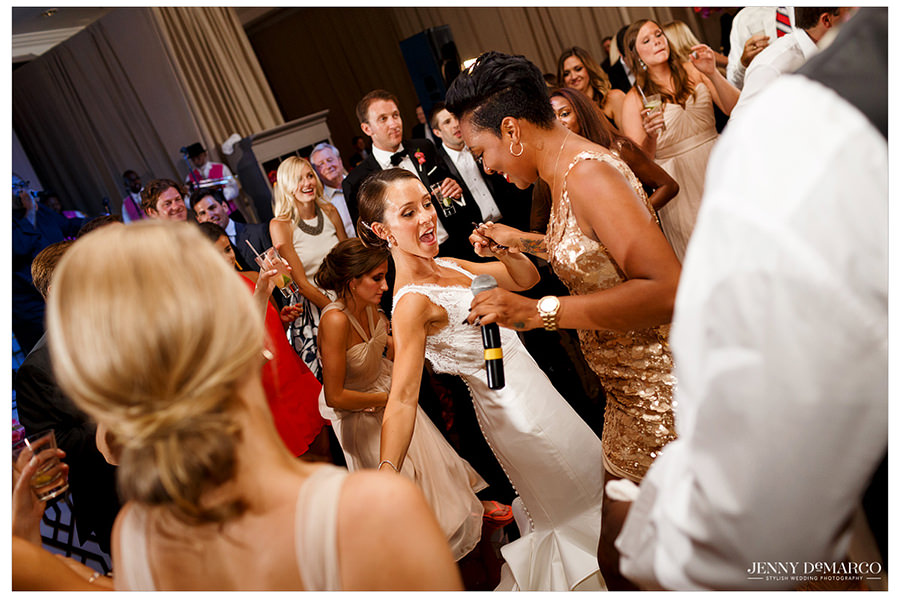 The lead singer from the band joins the bride and dances with her as they both sing into the microphone.