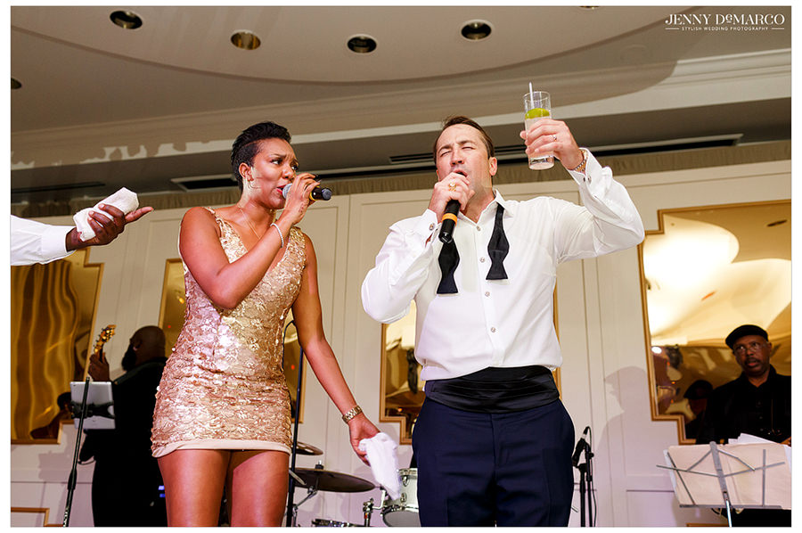 The groom gets on stage and sings along with the lead singer of the band while holding up his drink.