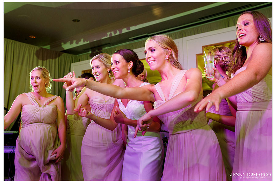 The bridesmaids dance around the bride and watch the other guests dancing around.