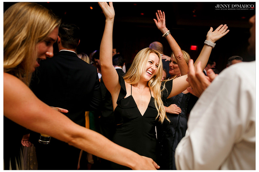 A guest throws her arms up while she dances with her friends.