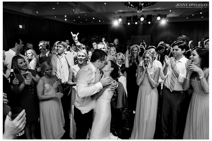 A black and white photo of the bride and groom kissing as their friends and family gather to cheer and clap.
