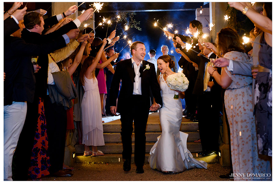 The bride and groom make their exit from the reception while their guests watch and hold sparklers to congratulate them.