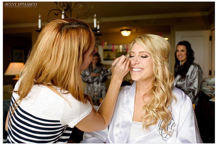 The bride smiles while she gets her makeup done.