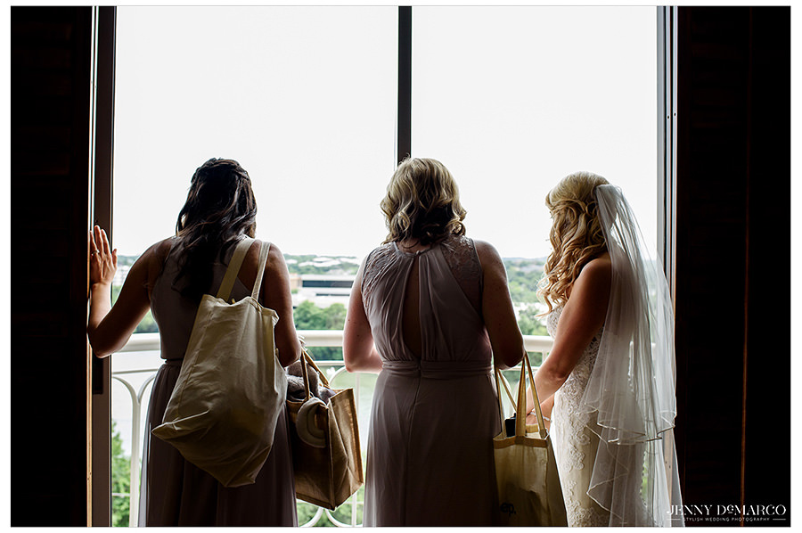The bride and her wedding party look out of a window before the wedding.