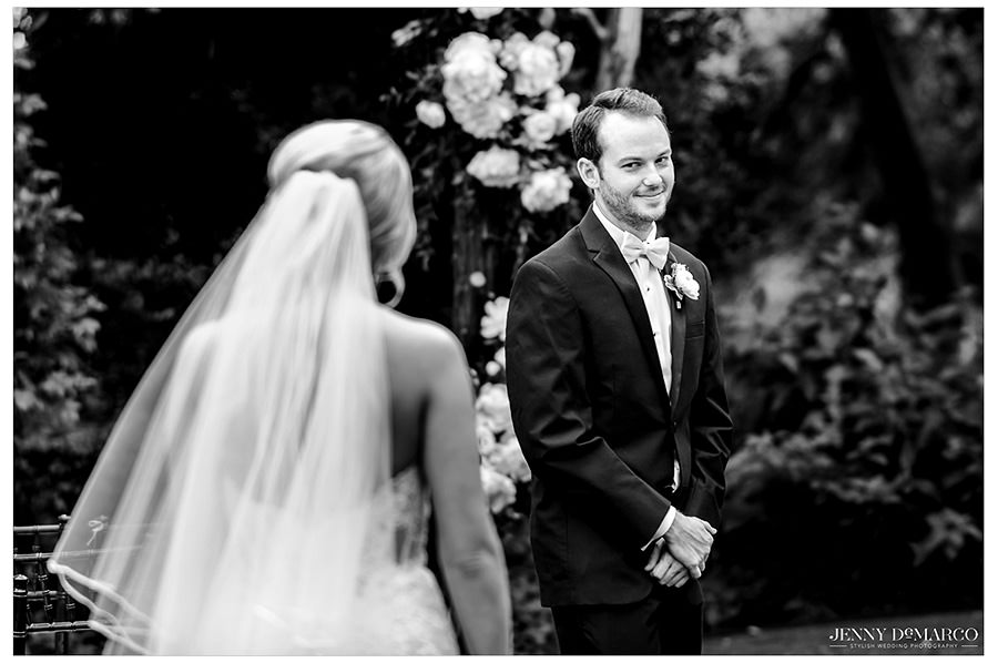 The groom smiles as he turns and sees his bride for the first time.