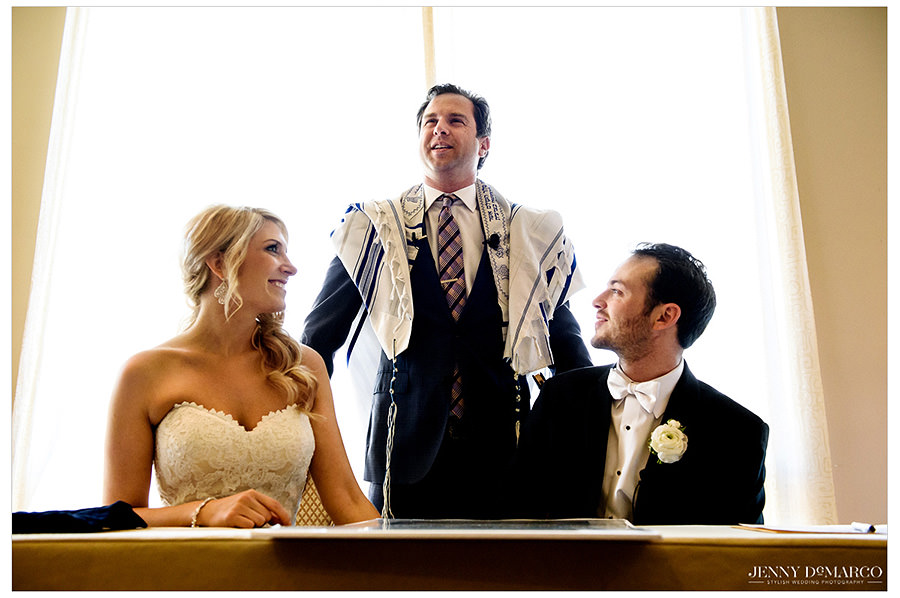 The rabbi stands behind the bride and groom while performing the ketubah.