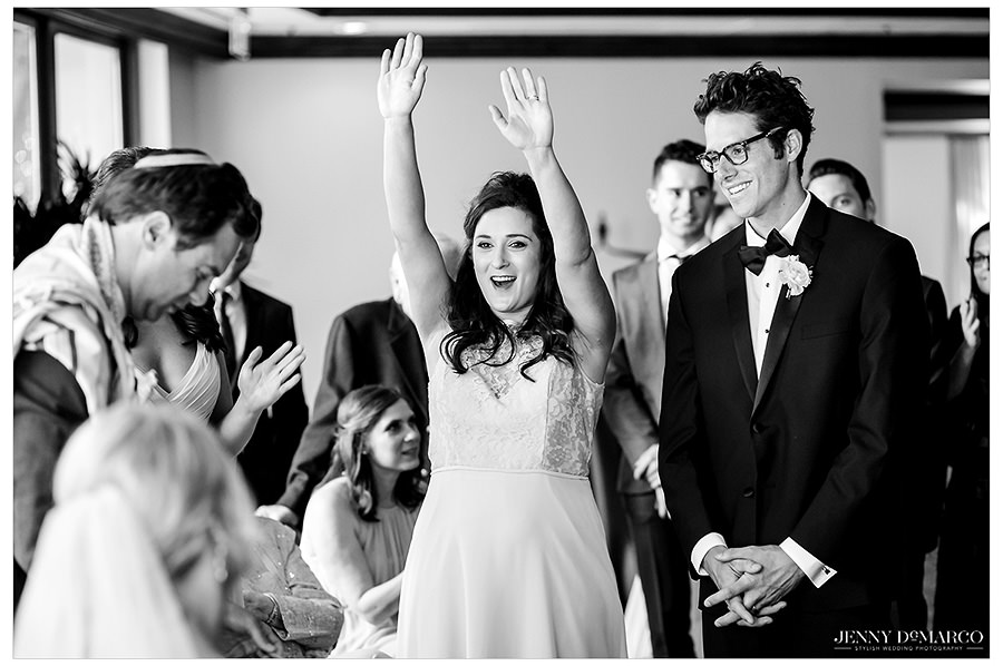 The wedding party cheers during the ketubah.
