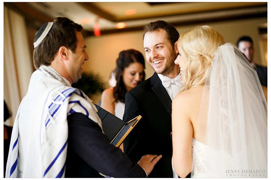 The bride and groom smile at the rabbi during the ketubah.