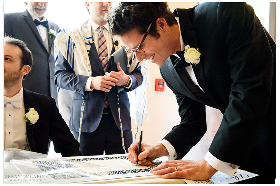 The wedding party signs the ketubah.