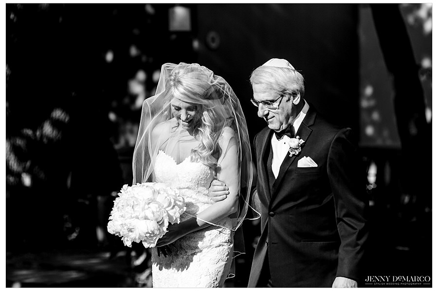 Black and white image of the bride and her father walking down the aisle.