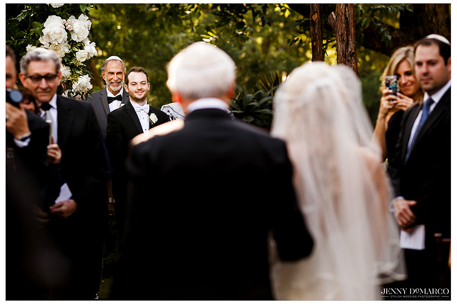 The groom smiles as he watches his bride walk down the aisle.