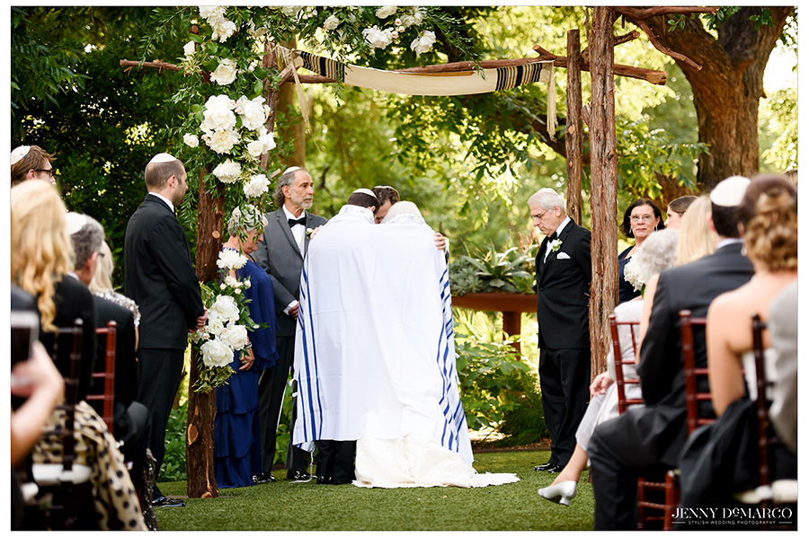 The bride and groom are wrapped in a tallit during their wedding ceremony.