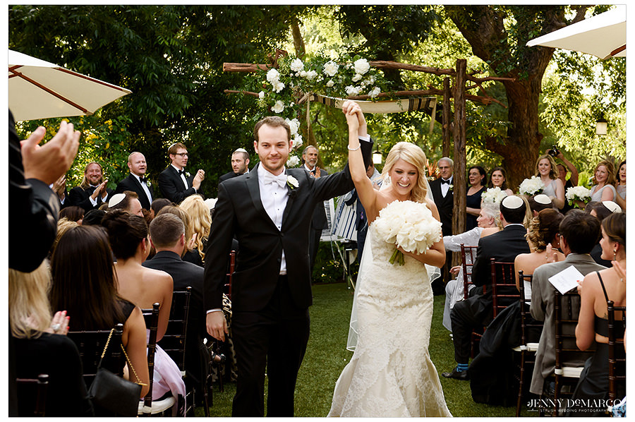 The bride and groom smile and hold hands in the air as they walk down the aisle as husband and wife.