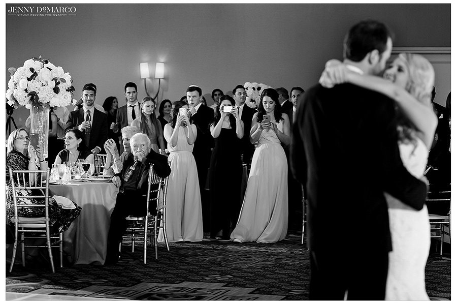 Guests look on as the bride and groom have their first dance.