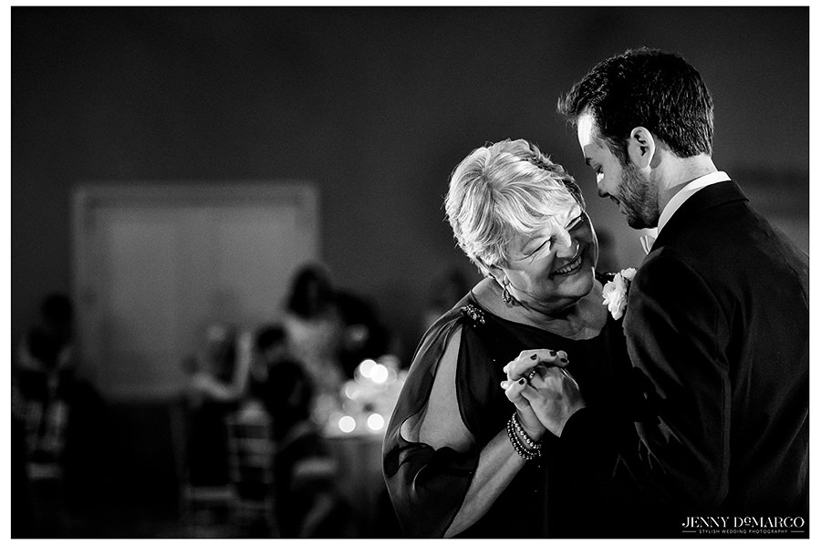 Black and white photo of the groom dancing with his mother.