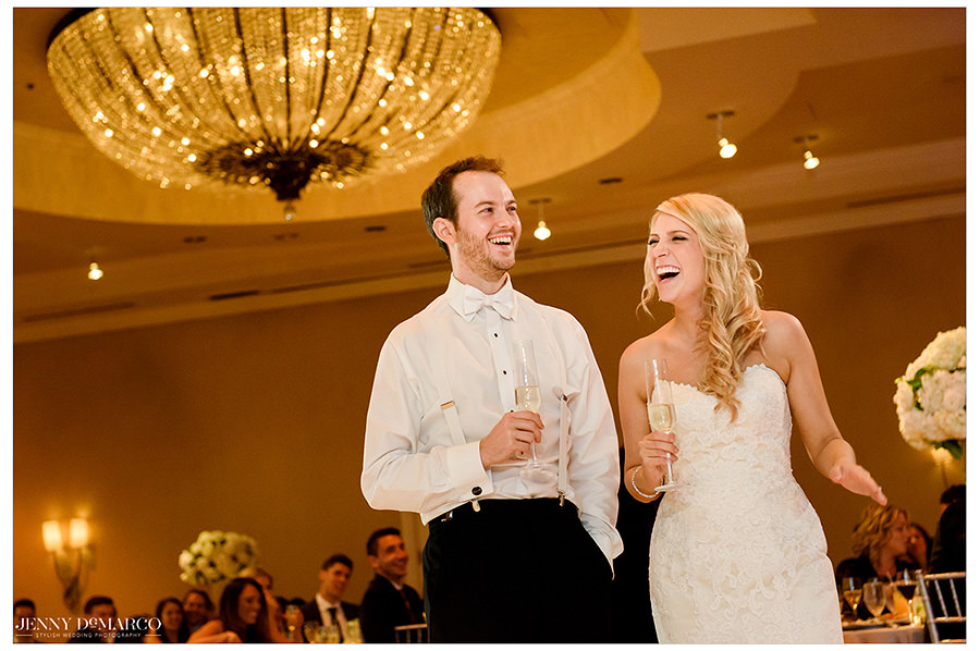 The bride and groom laughing during speeches.