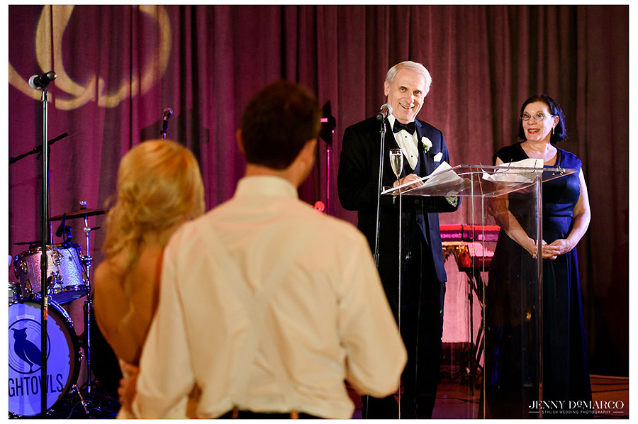 The bride and groom look on as the groom's father makes a speech.