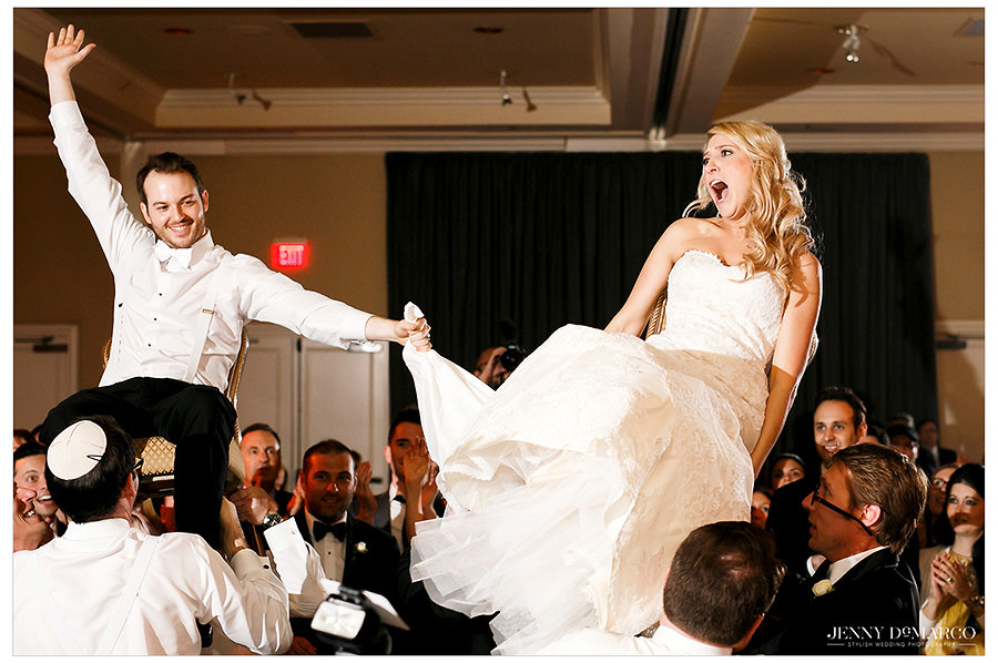The bride and groom are lifted on chairs during the Hora.
