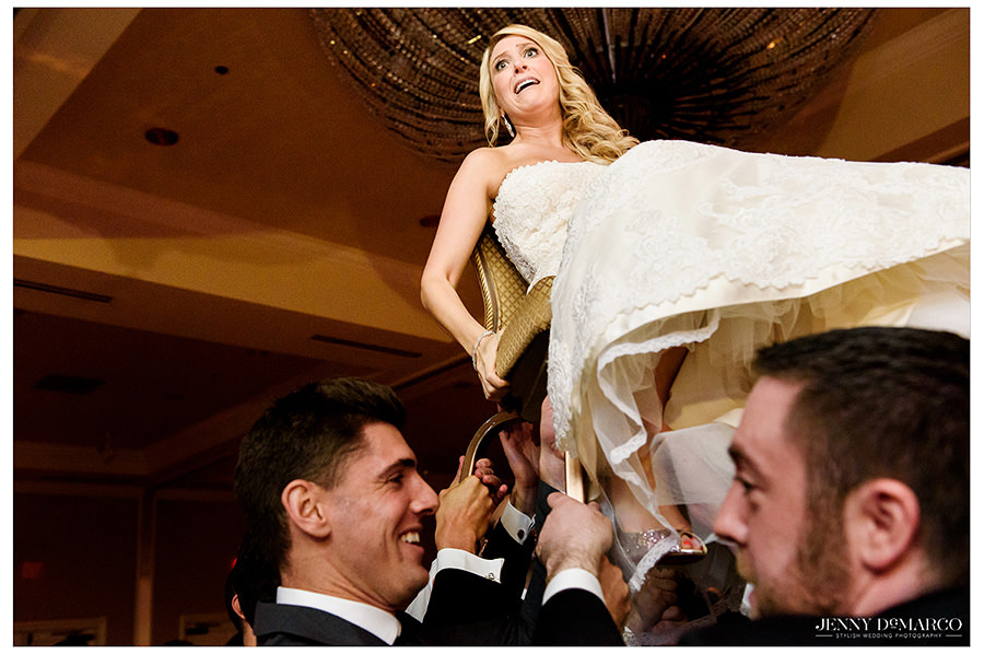 The bride makes an uneasy smile as she holds on to the chair she is lifted on.