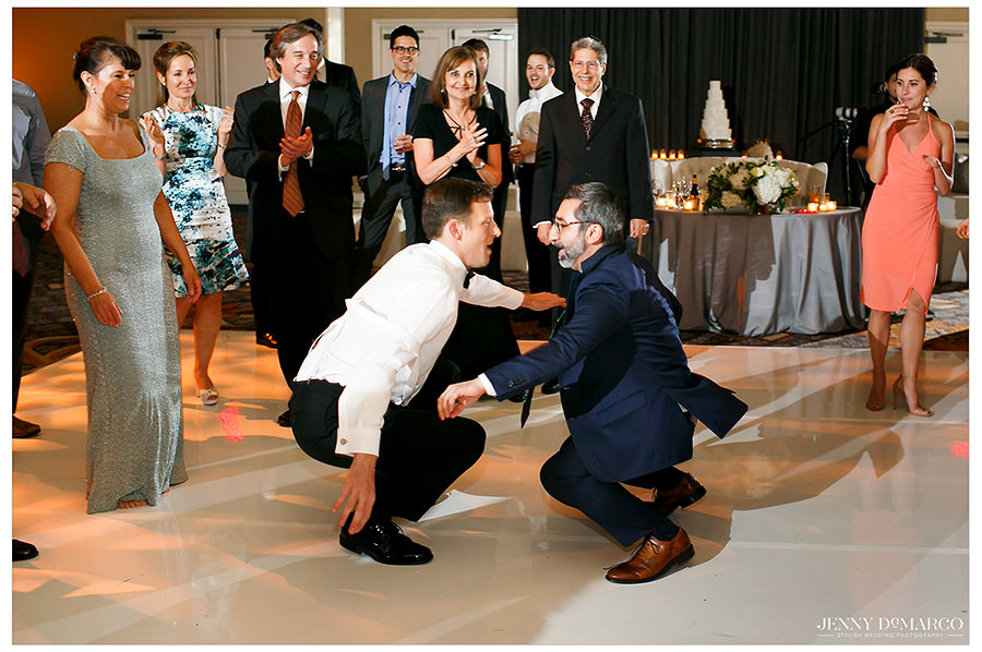 Two men dance low to the ground during the reception.