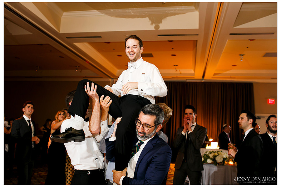 The groom is lifted by friends and family during the reception.